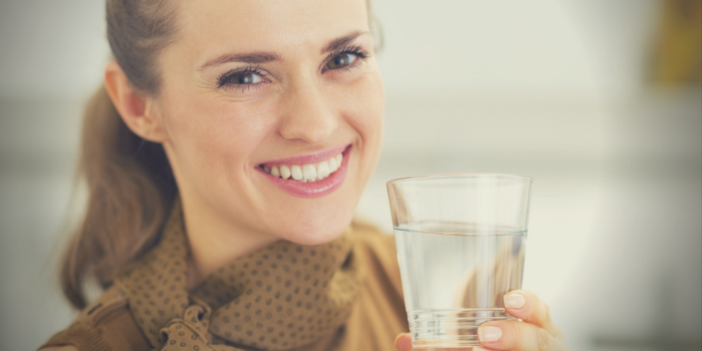 girl smiling with glass of water - water filtration systems